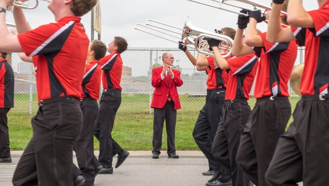 Port Huron High School principal Michael Palmer claps to the fight song as the band marches past him during the homecoming parade Oct. 6.