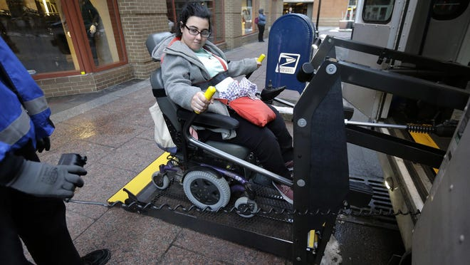Sarah Kaplan, of Lynn, Mass., rides an elevator April 5 to board a bus outside her workplace in Boston. Transit systems in major U.S. cities are required by federal law to provide specialized services for disabled passengers. Steve Senne/AP