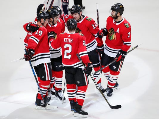 Chicago Blackhawks center Jonathan Toews (19) celebrates with teammates after scoring against the Columbus Blue Jackets during the third period of a preseason NHL hockey game Saturday, Sept. 23, 2017, in Chicago. (AP Photo/Kamil Krzaczynski)