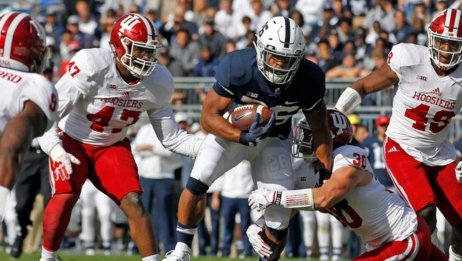 Penn State's Saquon Barkley (26) is brought down by Indiana's Chase Dutra (30) during the first half of an NCAA college football game in State College, Pa., Saturday, Sept. 30, 2017. (AP Photo/Chris Knight)