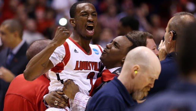 Russ Smith is held up by assistant coach Kevin Keatts as they celebrate Louisville's win against Duke during the Midwest Regional Final in March of 2013.
