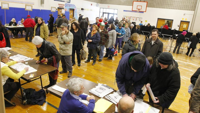 Lines form in alphabetical order as Irondequoit residents vote in a public referendum to authorize the construction of a new central library on the town hall campus at Christ the King School in Irondequoit on Saturday.