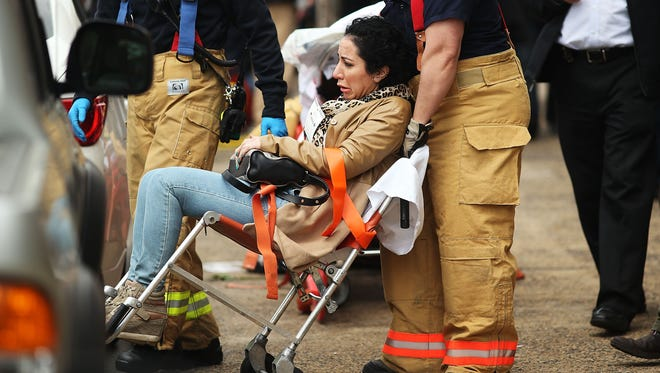 A woman is helped by New York City firefighters after being evacuated from an emergency staircase following an F train derailment on May 2 in the Woodside neighborhood of the Queens borough in New York City.