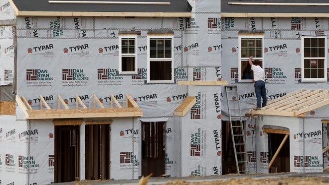 A construction worker installs a window on a new home in Zelienople, Pa., in March.