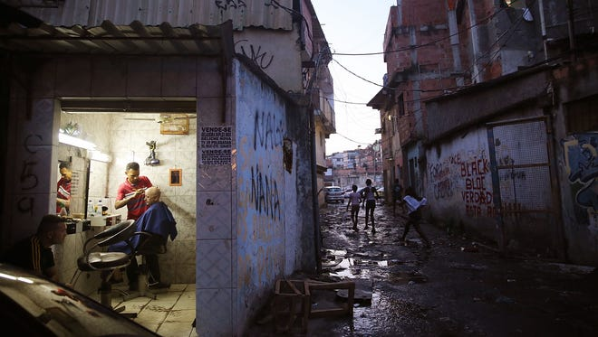 A man gets a haircut in a local business near the remains of demolished homes in Rio de Janeiro.