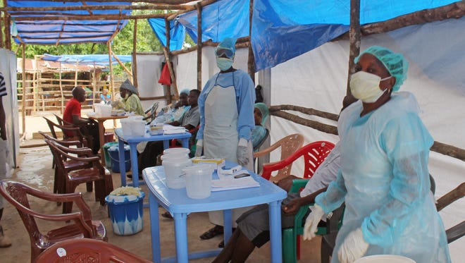 Medical personnel take care of Ebola patients in a clinic in the Kenema District on the outskirts of Kenema, Sierra Leone, on July 27.