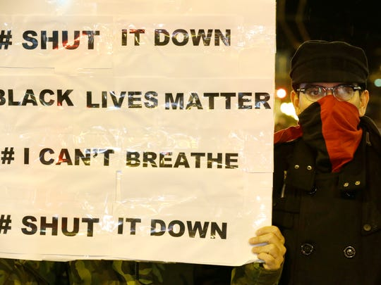 A protester stands next to a sign listing popular hashtags