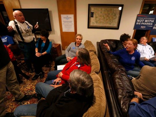 Hillary Clinton supporter John Means (left) argues with Bernie Sanders supporter Carrie Kimrey (right) over Sanders' electability Feb. 1, 2016, at a home caucus site in Rippey, Iowa.