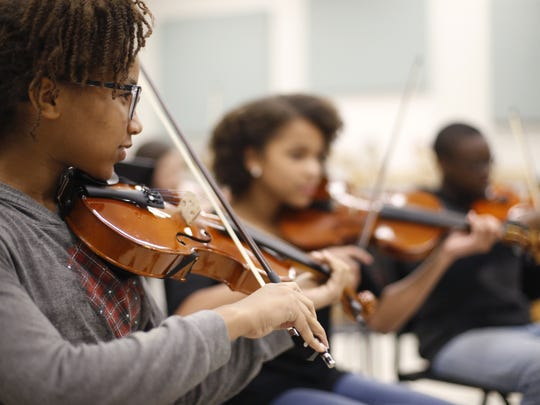 Amarachi Thompson, left, leads the violin section in a rendition of the Ghostbusters theme song during class at Raa Middle School.