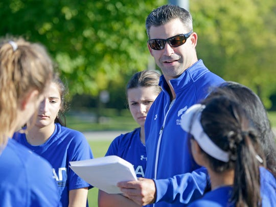 Reagan tennis coach Eli Kelley talks to his team during the subsectional match at South Milwaukee High School
