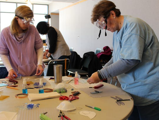 Participants work with stained glass in a past Minnetrista