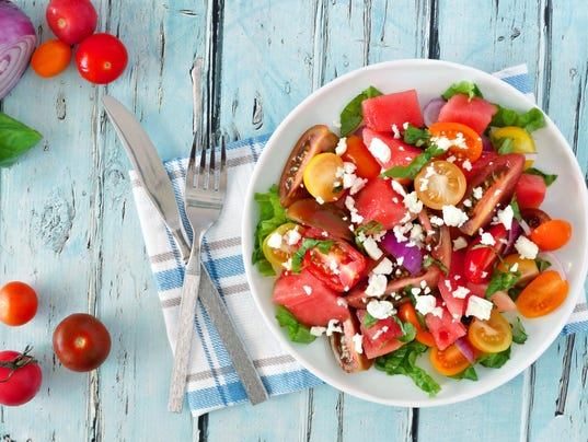 Watermelon and tomato salad with feta, overhead on blue wood