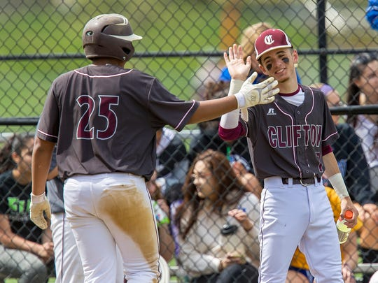 Clifton freshman Justin Rivera (25) is congratulated by senior teammate Mike Algieri after scoring one of his three runs in Saturday's Passaic County baseball quarterfinal win at Hawthorne.