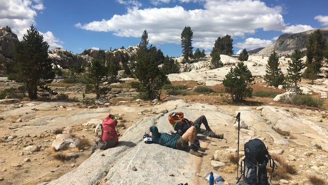Two exhausted backpackers take a break near the John Muir Trail at Evolution Lake.