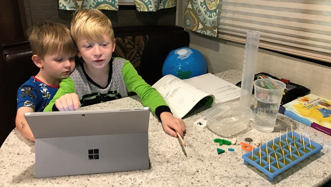 Kindergartner Tristan Logue, 6, logs onto his virtual school while on a yearlong, cross-country trip. His brother Jasper, 3, follows along.