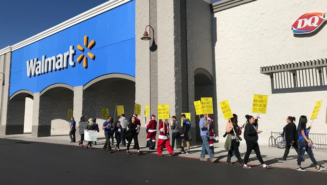 Protesters dressed in holiday costumes rally in front of a Walmart in Phoenix on Dec. 7, 2017.