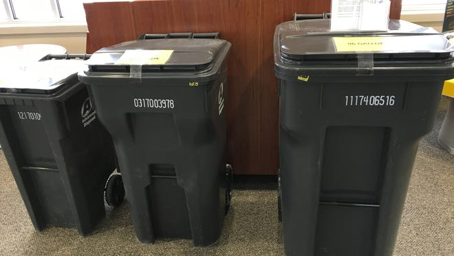 Trash cans on display at the Everett Roehl Marshfield Public Library. The city will be distributing new trash and recycling carts to residents in April.