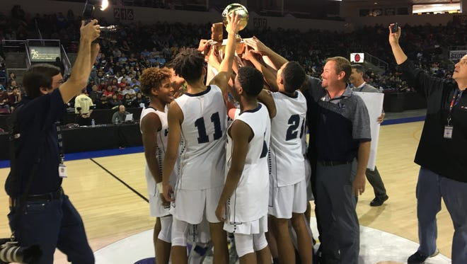 The Tucson Gregory School boys basketball team lifts the 1A trophy in celebration after winning 65-46 over Fort Thomas Apaches at the Prescott Event Center on Saturday.