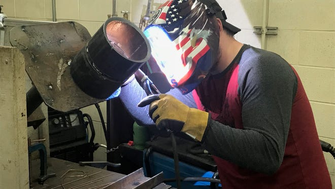 Cody McNiel, a welding student at Cisco College, has his mask illuminated by the fire generated by the welding torch he's using during class Thursday, April 12, 2018.