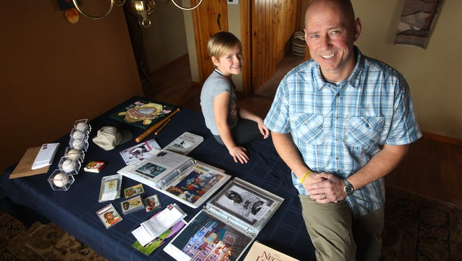Jeff Klein with his daughter Makayla, 8, with some of the memorabilia collected about the baseball Negro leagues. Jeff began collecting items after helping Makayla with a school project.