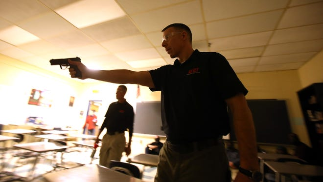 ALICE instructor, Detective Derek Jones of the Georgetown (MA) Police Department plays the bad guy pointing and firing an Airsoft pistol during a traditional lockdown scenario during ALICE training, preparing for a school shooter with local law enforcement and educators throughout the halls of Roxbury High School. March 29, 2016. Roxbury, N.J.
