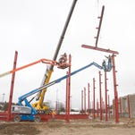 Girders suspended from a crane are aligned in the construction of the Livingston County Jail expansion.