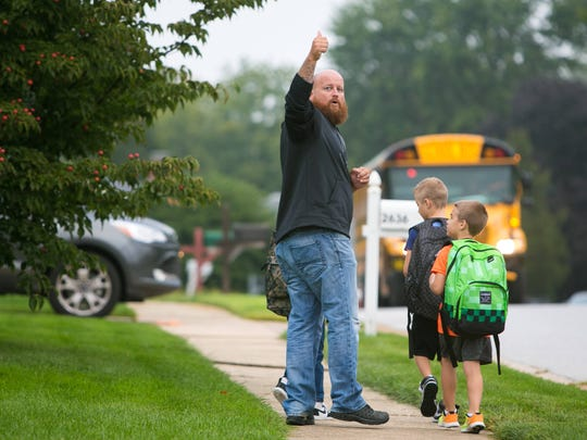 Jeremy Pimer gives a thumbs up to his wife as he walks his son Jacob, along with his friends Landon and Madden, to school. The kids have to walk on a busy road to get to school every morning since they live one to two miles from school and therefore do not qualify for bus service.