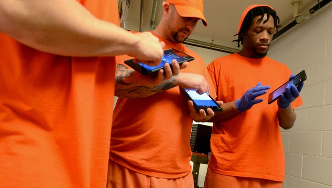 Inmate Eric McCall, right, plays on his new tablet Monday, Dec. 28, at the Sanilac County jail in Sandusky. Inmates are using these on a free trial basis at the jail.