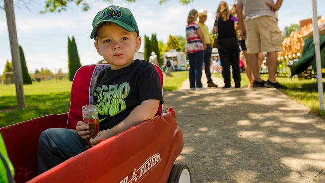 Brayden Abney, 2, of Melvin, eats some candy Sunday, June 12, during the Brown City Days Soybean Festival.
