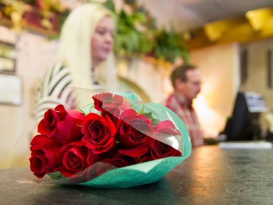 Darcy Culligan, left, and co-owner Mike Jewel both of Evansville, work behind the counter near customer's bouquet of red roses at Cottage Florist & Gifts in Evansville, Thursday, March 16, 2017. Cottage Florist & Gifts recently moved to their new location in the North Park Shopping Center after 17 years on Lincoln Ave.