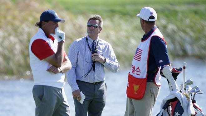 Phil Mickelson confers with his caddie Jim Mackay and rules offical Gary Young after Mickelson played an incorrect ball during his match on Day 2 at the Presidents Cup.