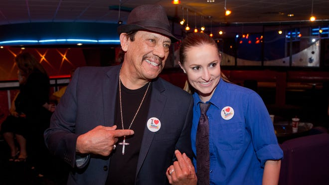 "Actor Danny Trejo poses while wearing an ""I Love Allen Theatres"" button with Allen manager Erin Whitehead at the Cineport 10 Theatre during the Las Cruces International Film Festival on March 3, 2016. Trejo attended the festival as the ""Outstanding Achievement In Entertainment"" award winner and introduced screenings of his film Machete at the Cineport."