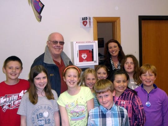 Bill Schaefer of the Sturgeon Bay Masonic Lodge, Julie Davis, Chief Professional Officer of the Boys and Girls Club, and youth members of the Boys and Girls Club stand with the newly installed AED machine.