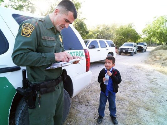 A Border Patrol agent with Alejandro, 8, who traveled by himself across the Rio Grande. Border Patrol agents process a group of 22 migrants from Honduras and Guatemala including an 8-year-old boy during routine U.S. Customs and Border Protection operations in the Rincon region of the Rio Grande River between the Hidalgo International Bridge and the Anzalduas International Bridge near McAllen, Texas, on Wednesday, June 18, 2014. (Photo by Jennifer Whitney)