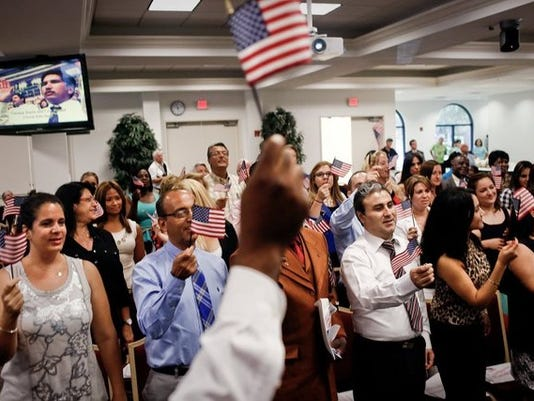 """In this June 2014 file photo, 50 newly-certified U.S. citizens sing the song, """"Proud To Be An American"""" at a naturalization ceremony at Hodges University in Naples. (Scott McIntyre/File)"""