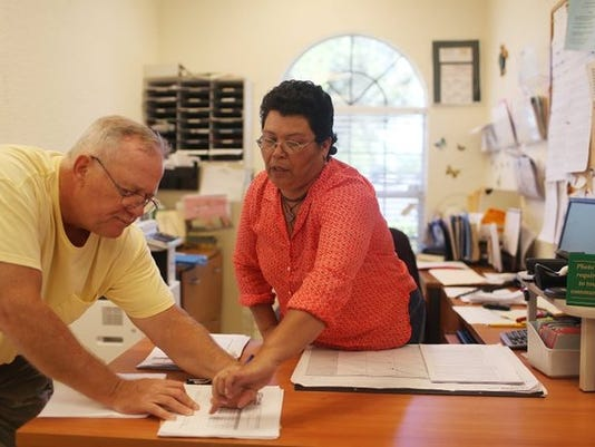 Karl Thomann, left, writes his signature in support of new legislation allowing undocumented immigrants to get drivers licenses while in the leasing office where Margarita Claro, right, works at Wild Pines Apartments on October 17, 2014, in Naples, Fla. The Florida Immigrant Coalition believe that everyone should have the right to safety behind the wheel but almost one million Floridians cannot get a license or insurance because of the immigration system