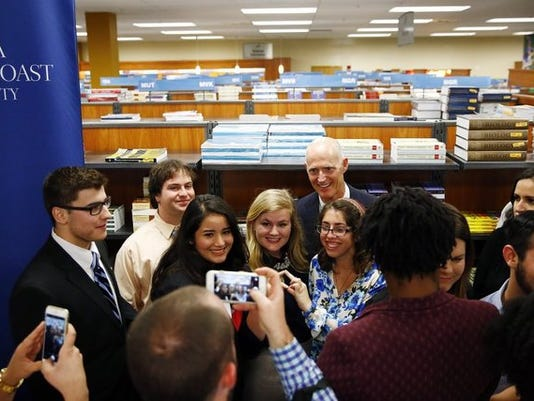 Florida Governor Rick Scott photographs with students Friday, Jan. 30, 2015 at the FGCU bookstore in Estero, Fla. Scott will highlighted his proposal to eliminate the sales tax on college textbooks and a proposal to expand the Bright Futures Scholarship program. He met with students, faculty and board of trustee members and media for about an hour. (Corey Perrine/Staff)
