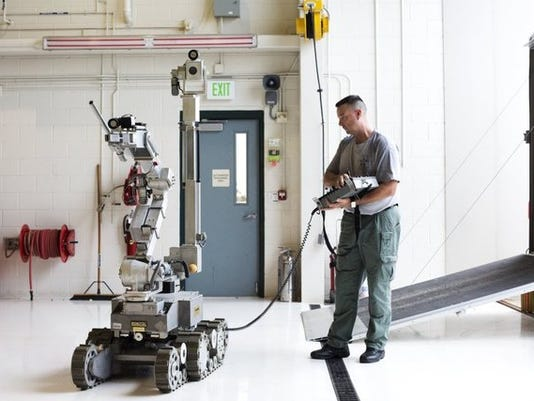 Cpl. Todd Sanner demonstrates how the Collier County bomb squad's Remotec ANDROS remote control robot works at the Collier County Sheriff's Office Special Operations Center in Naples on May 13, 2015. (Carolina Hidalgo/Staff)