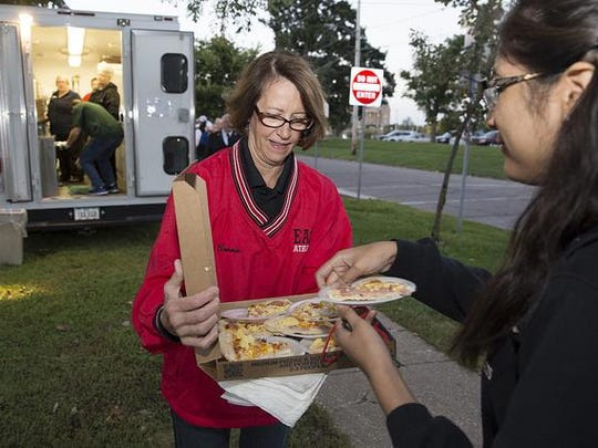 Des Moines school board member Connie Boesen serves an East High student some breakfast pizza at the school's weekly Fuel Up First breakfast.