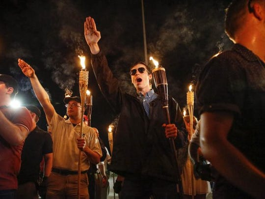 Multiple white nationalist groups march with torches through the UVA campus in Charlottesville on Aug. 11, 2017.
