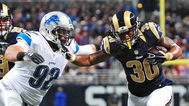Dec 13, 2015; St. Louis, MO, USA; St. Louis Rams running back Todd Gurley  stiff arms Detroit Lions defensive tackle Haloti Ngata during the second half at the Edward Jones Dome.