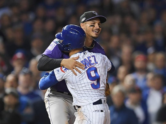 Javier Baez, No. 9, of the Chicago Cubs hugs Nolan Arenado, No. 28, of the Colorado Rockies in the 11th inning during the National League Wild Card Game at Wrigley Field on October 2, 2018, in Chicago, Illinois.