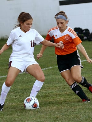 Woodbridge's Kiley Dugan, left, and Marlington's Laney Hess during action at Marlington last season.