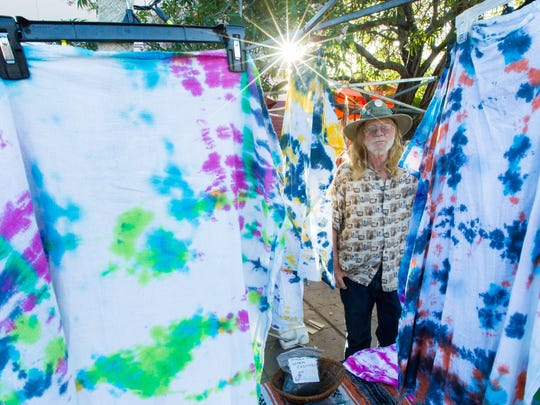 """""""Travelin Terry"""" Thomas, stands among his display of tie-dye  apparel on Wednesday, May 11, 2016, during the first evening first evening of the Las Cruces Farmers and Crafts Market. """"I don't come out here to make money, I come to make friends,"""" said Thomas."""
