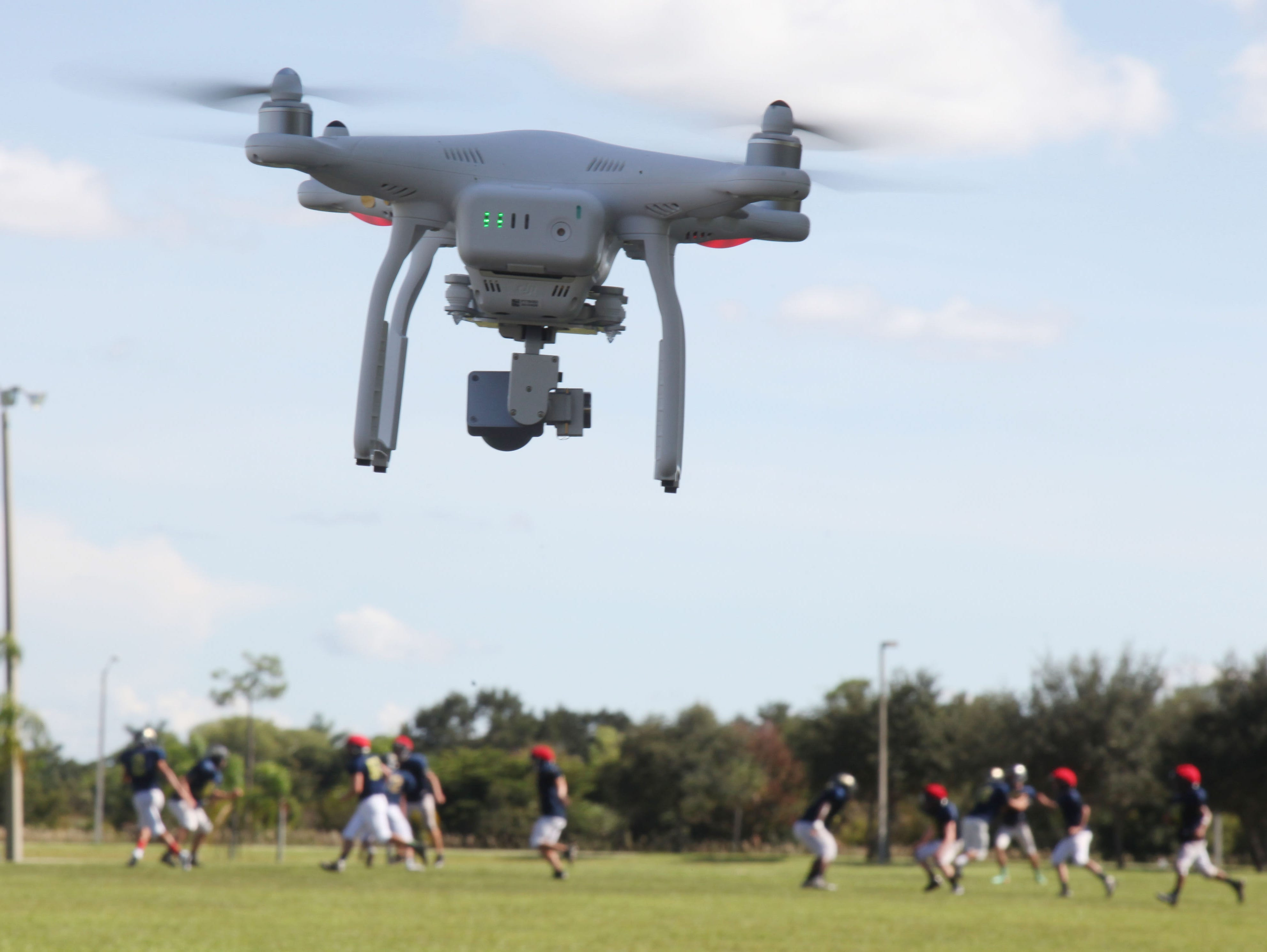 A DJI Pantom 3 Professional drone operated by Mark Harden flies over the practice field at Southwest Florida Christian Academy.