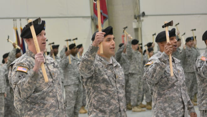 Maj. James Brogan (left), Maj. Toby Jimenez and Maj. Steve Robinson raise rifleman's hatchets at a ceremony reflagging the 4th Brigade 10th Mountain Division, known as the Patriots, as the 3rd Brigade, 10th Mountain Division at Fort Polk Tuesday, Feb. 24, 2015. The hatchets symbolize the American Colonial spirit.