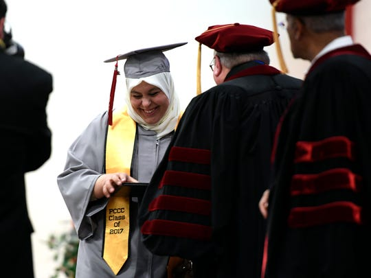 Makarem Abdeljawad of Paterson smiles as she takes a diploma from PCCC President Steven Rose during commencement on Thursday, May 18, 2017.