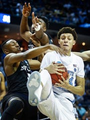 University of North Carolina forward Justin Jackson (right) grabs a rebound away from Butler University teammates Avery Woodson (left) and Kelan Martin (back) during first half action of their NCAA tournament Sweet Sixteen matchup at the FedExForum.