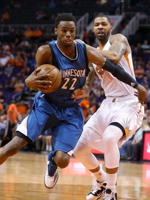 Minnesota Timberwolves forward Andrew Wiggins (22) drives past Phoenix Suns forward Marcus Morris during the first quarter Wednesday in Phoenix.