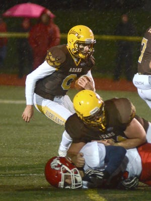 As a teammate blocks a Romeo player, below, Rochester Adams quarterback Zach Soldan starts a run during the 26-17 win in the Division 1 playoff game on Friday, Oct. 27, 2017, in Rochester.
